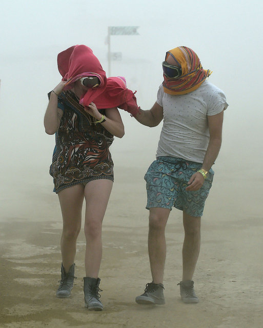 Robynne Rowlinson, left, and James Bisset, both from South Africa, walk through a morning dust storm at Burning Man on the Black Rock Desert in Gerlack, Nev. on Saturday, August 29, 2015. (Photo by Andy Barron/The Reno Gazette-Journal via AP Photo)