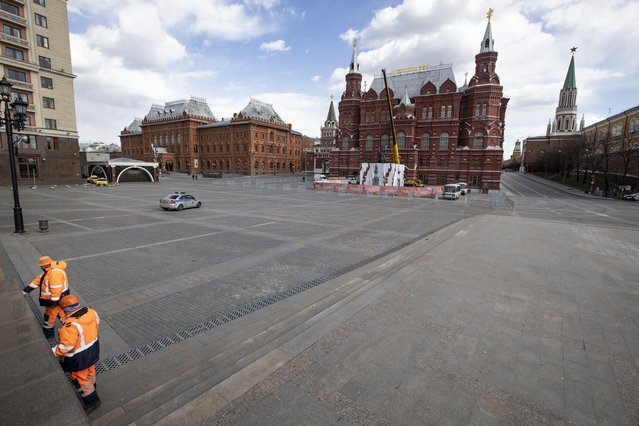 Municipal workers clean a marble wall in an empty Manege Square near Red Square in Moscow, Russia, Thursday, April 23, 2020. The authorities have ordered most city residents except those working in essential sectors to stay home through April 30 to stem the coronavirus outbreak. The new coronavirus causes mild or moderate symptoms for most people, but for some, especially older adults and people with existing health problems, it can cause more severe illness or death. (Photo by Alexander Zemlianichenko/AP Photo)