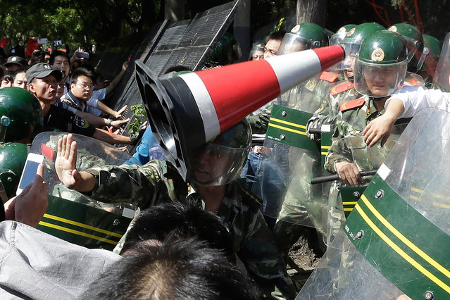 A Chinese paramilitary policeman is hit by a traffic cone as he tries to hold back protesters from storming the Japanese embassy in Beijing, China, on September 15, 2012. (Photo by Ng Han Guan/AP Photo)