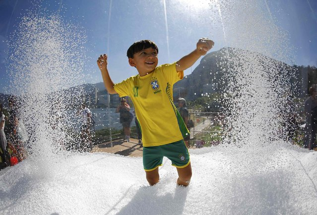 A boy wears a Brazil football shirt as he plays in a display at the Switzerland house in Lagoa, Rio de Janeiro, Brazil on August 1, 2016. (Photo by Ivan Alvarado/Reuters)
