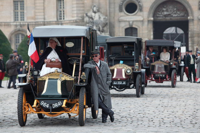 """WWI enthusiasts dressed in French World War I military uniforms, stand next to the """"Taxis of the Marne"""", during a commemoration parade, in Paris, Sunday, September 7, 2014. Weeks after World War I erupted, with the capital under threat from German invaders, necessity forced French military chiefs to dream up a new way for soldiers to travel to the front lines: by taxi. This weekend, France honors the centennial of the """"Taxis of the Marne"""", which have become the stuff of legend for millions of French school kids present and past. (Photo by Thibault Camus/AP Photo)"""