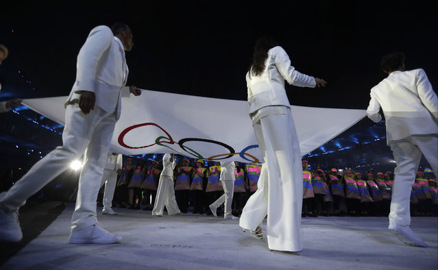 Flab bearers march with the Olympic flag during the opening ceremony for the 2016 Summer Olympics in Rio de Janeiro, Brazil, Friday, Aug. 5, 2016. (AP Photo/David Goldman)