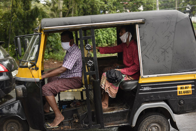 People wearing masks ride on a auto-rickshaw during extended lockdown in Kochi, southern Kerala state, India, Monday, May 18, 2020. India on Monday saw a slow trickle of people returning outdoors and thin traffic on its roads in some states, a day after the federal government extended the nationwide coronavirus lockdown to May 31 but eased many restrictions to restore economic activity. (Photo by R S Iyer/AP Photo)
