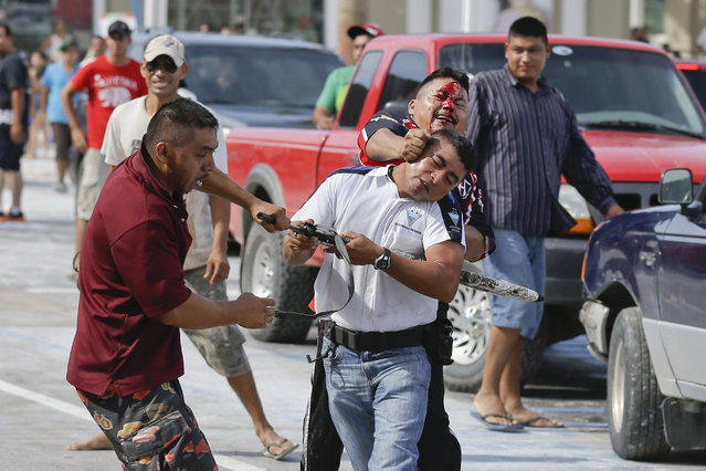 A man holding an air rifle in a white jersey fights with two other men as he tries to stop looters from storming into the Mega Supermarket in Los Cabos, Mexico, Tuesday, September 16, 2014. According to employees the supermarket donated all the food in the store and established a system by which every person had 5 minutes to get whatever they could for free. Fights broke as other people inciting the crowd to loot. (Photo by Victor R. Caivano/AP Photo)