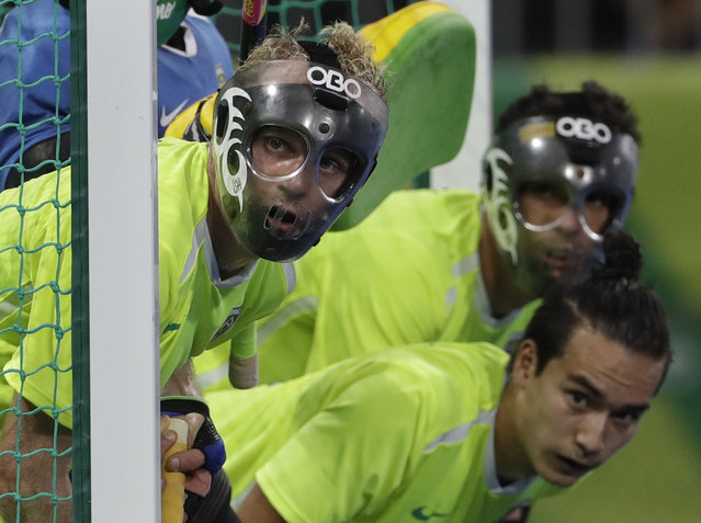 Brazilian players wear their protective face masks as they prepare for a free shot from the British team, during a men's field hockey match, at 2016 Summer Olympics in Rio de Janeiro, Brazil, Tuesday, August 9, 2016. (Photo by Hussein Malla/AP Photo)