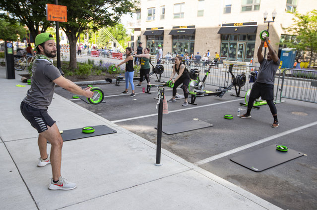Jacob Morden leads a fitness class on a closed street in downtown Indianapolis, Friday, May 22, 2020. The city closed several streets to traffic to accommodate larger outdoor areas for restaurants to provide for social distancing and the gym was able to take advantage of the closure to teach outdoor class. Gym as not yet allowed to open. (Photo by Michael Conroy/AP Photo)
