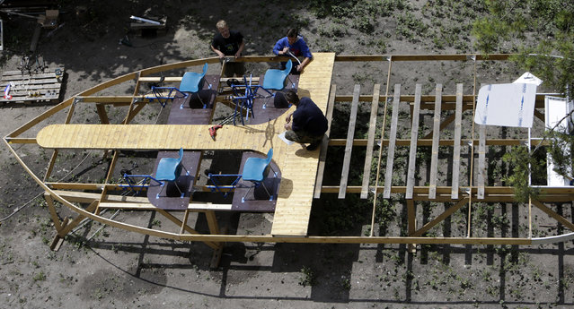 (L-R) Jakub Bures, Jan Kara and Jan Holan attach plastic garden chairs to a wooden frame as they build a boat in their yard in Nymburk July 1, 2014. (Photo by Rene Volfik/Reuters)