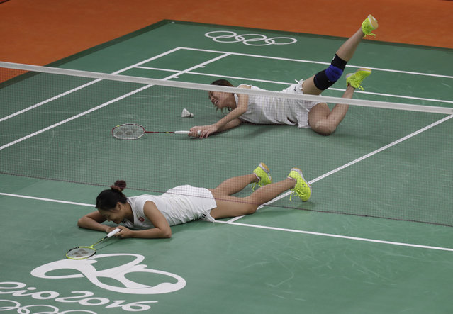 Hong Kong Poon Lok Yan, right, and Tse Ying Suet fell as they fail to return a shot during a Women's doubles match against Malaysia's Vivian Hoo Kah Mun and Woon Khe Wei at the 2016 Summer Olympics in Rio de Janeiro, Brazil, Friday, August 12, 2016. (Photo by Kin Cheung/AP Photo)