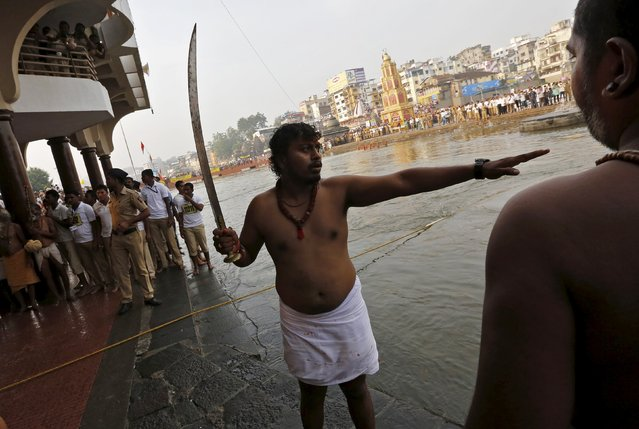 "A sadhu or a Hindu holy man holds a sword as he secures the bathing area for others on the banks of Godavari river during the second ""Shahi Snan"" (grand bath) at Kumbh Mela or Pitcher Festival in Nashik, India, September 13, 2015. (Photo by Adnan Abidi/Reuters)"