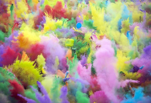 Festival goers enjoy the color party, when participants throw colored powder at each other, at the 24th Sziget (Island) Festival on Shipyard Island, Northern Budapest, Hungary, Saturday, August 13, 2016. The festival is one of the biggest cultural events of Europe offering art exhibitions, theatrical and circus performances and music concerts over eight days. (Photo by Balazs Mohai/MTI via AP Photo)