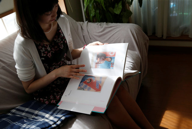Chunhun, the leader of Japan's North Korea fan club called sengun-joshi, or military-first girls, looks at a photobook of North Korean art in Tokyo, Japan on November 2, 2017. (Photo by Toru Hanai/Reuters)