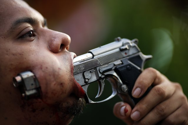 A devotee of Ban Tha Rua Chinese shrine with a gun pierced through his cheek takes a part in a procession celebrating the annual vegetarian festival in Phuket October 19, 2012. The festival celebrates the local Chinese community's belief that abstinence from meat and various stimulants during the ninth lunar month of the Chinese calendar will help them obtain good health and peace of mind. (Photo by Damir Sagolj/Reuters)