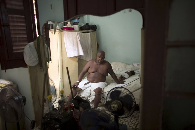 Public park caretaker Idalberto Diaz, 55, rests in a bed beside his 6-month-old granddaughter Lia, before a ceremony in a house known as Cabildo, or religious house by Santeria tradition, in downtown Havana, August 7, 2015. (Photo by Alexandre Meneghini/Reuters)