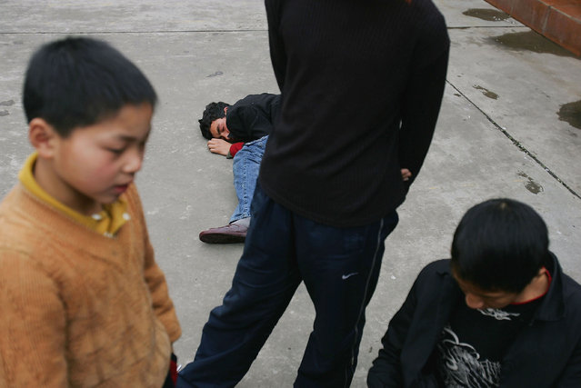 A Chinese boy (C) faints after refusing to eat at an assistance center February 23, 2005 in Shenzhen, Guangdong Province, China. (Photo by Cancan Chu/Getty Images)