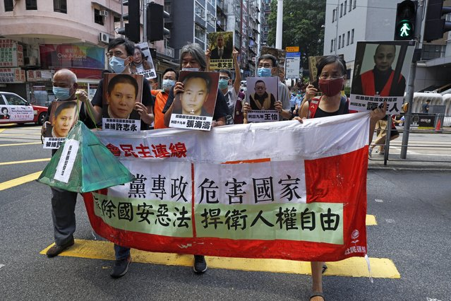 """Pro-democracy demonstrators hold up a banner and portraits of jailed Chinese civil rights activists, lawyers and legal activists as they march to the Chinese liaison office in Hong Kong, Thursday, June 25, 2020. The banner read """"One-party dictatorship harms the country, abolish the national security law and defend human rights and freedom in Hong Kong"""". (Photo by Kin Cheung/AP Photo)"""