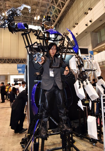 """A man wears the lightweight robot suit """"Skeletonics"""" which expands its users' motions two times larger at the CEATEC electronics trade show in Chiba, suburban Tokyo on October 7, 2014. (Photo by Yoshikazu Tsuno/AFP Photo)"""