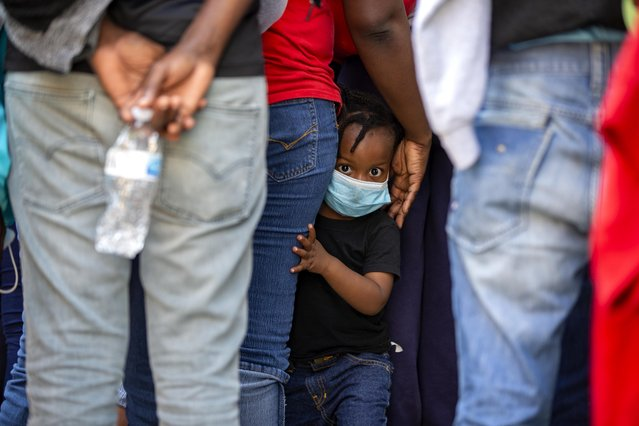 A child looks at the camera as Haitians who were deported from the United States line up as they arrive at a hotel where they will be quarantined as a measure against the spread of the new coronavirus, in Tabarre, Haiti, Thursday, April 23, 2020. (Photo by Dieu Nalio Chery/AP Photo)