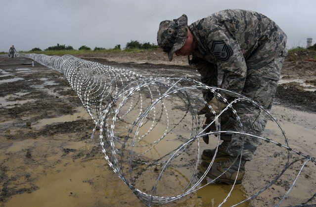 An US air Force soldier delimits with barbed wire the position of the next Ebola treatment center reserved for contaminated healthcare workers in Monrovia, on October 6, 2014, where the virus continues to claim more victims. Liberia is the country hit hardest by the largest Ebola outbreak on record, accounting for about two-thirds of the total 3,338 deaths recorded in the region since the beginning of the year. (Photo by Pascal Guyot/AFP Photo)
