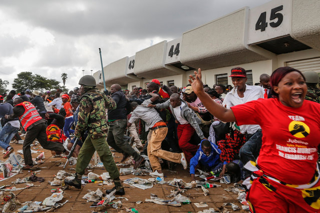People flee as they are beaten by police officers after trying to force their way into the stadium where President-elect Uhuru Kenyatta is about to arrive for his swearing-in ceremony in Nairobi, Kenya, 28 November 2017. Outside of the stadium, police fired tear gas to disperse the crowd who tried to force their way into the venue while Kenyatta and his deputy William Ruto were being sworn-in as President and deputy president respectively at an event attended by several African heads of states. Supporters of the opposition coalition the National Super Alliance and its presidential candidate Raila Odinga also clashed with police as they try to hold a rally in the capital. Local media reported at least three people have been shot as protesters engaged in running battles with police. (Photo by Dai Kurokawa/EPA/EFE)