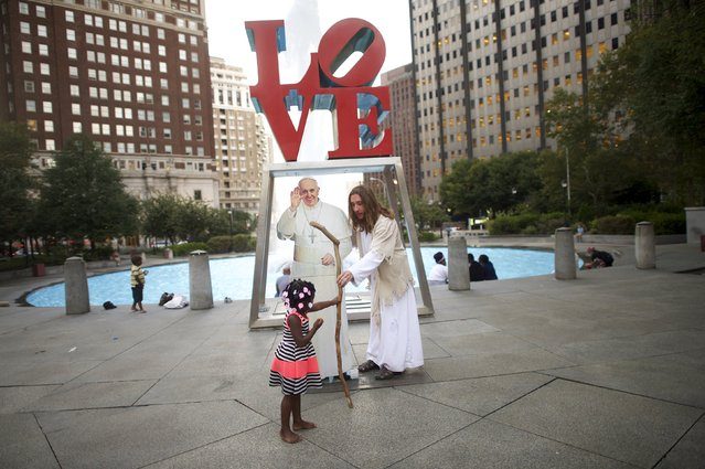 """Philly Jesus"", Michael Grant, hands his staff to a girl beside a cardboard cut-out of Pope Francis, at Love Park, in Philadelphia, Pennsylvania, September 16, 2015. (Photo by Mark Makela/Reuters)"