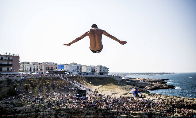 This handout photo released by Red Bull and taken on August 27, 2016 shows Mexico's Jonathan Paredes diving from the 27-metre-high platform during the first competition day of the fifth stop of the Red Bull Cliff Diving World Series at Polignano a Mare. (Photo by Dean Treml/AFP Photo)