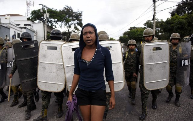 Military police stand guard next to supporters of opposition candidate Salvador Nasralla as they hold a protest march on December 6, 2017 in Tegucigalpa, Honduras. Honduras appeared set for a recount of its election Tuesday after incumbent President Juan Orlando Hernandez welcomed a demand by the opposition to re- open ballot boxes, a week into a crisis triggered by rigging claims. The small Central American nation of 10 million people has been plunged into uncertainty punctuated with clashes since the November 26 election pitting Hernandez against leftwing former TV presenter Salvador Nasralla, with both sides claiming victory. (Photo by Johan Ordonez/AFP Photo)