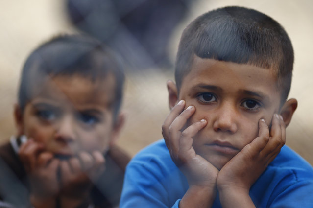 Kurdish refugee children from the Syrian town of Kobani sit behind a fence in a camp in the southeastern town of Suruc on the Turkish-Syrian border, October 19, 2014. (Photo by Kai Pfaffenbach/Reuters)