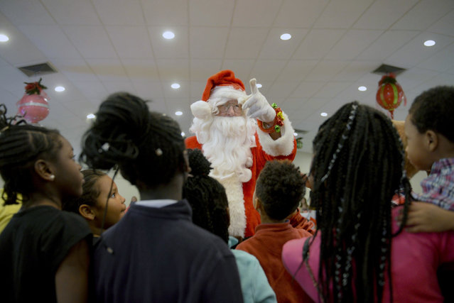 Children anxiously await as Santa Claus delivers individual gifts during the Savannah Elks Lodge #183 Christmas gathering, Sunday, December 17, 2017 in Savannah, Ga.. The Elks Lodge invited 175 children and their families from Hunter Army Airfield, Ft. Stewart, Safe Shelter, Salvation Army and the local Aidmore Foster Home program out to their Southside lodge to celebrate the season. (Photo by Will Peebles/Savannah Morning News via AP Photo)