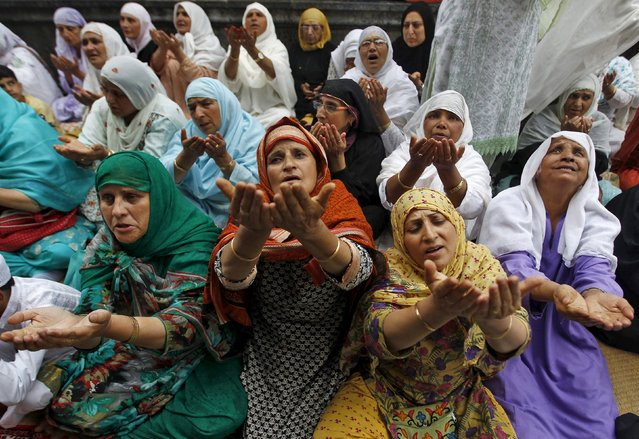 Kashmiri Muslim women raise their hands as they pray at the shrine of Mir Syed Ali Hamdani, a Sufi saint, during a religious festival to mark Saint Hamdani's birth anniversary in Srinagar September 21, 2015. (Photo by Danish Ismail/Reuters)