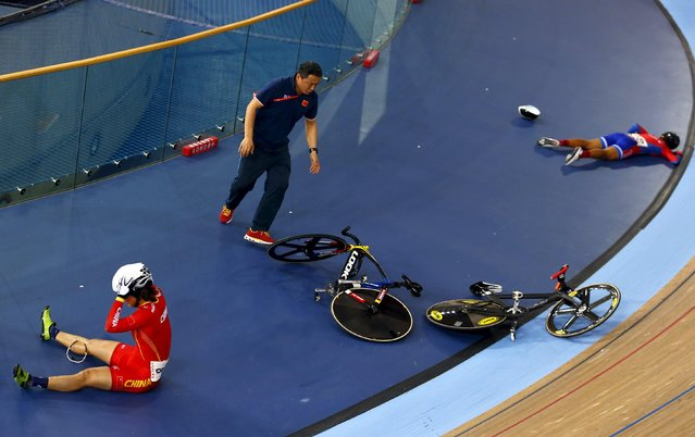 An official rushes to move bicycles as Luo Xiao Ling of China (L) and Marlies Mejias Garcia of Cuba lie on the track after crashing in the women's omnium elimination race at the UCI World Track Cycling Championships in London, Britain, March 5, 2016. (Photo by Andrew Winning/Reuters)