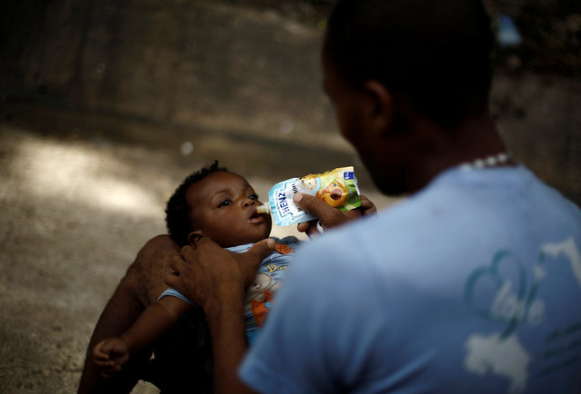 An African migrant stranded in Costa Rica feeds his daughter at makeshift camp at the border between Costa Rica and Nicaragua, in Penas Blancas, Costa Rica, September 8, 2016. (Photo by Juan Carlos Ulate/Reuters)