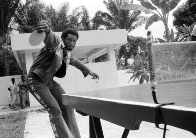 Heavyweight champion George Foreman makes a backhand slam as he relaxes with a game of table tennis at the poolside of his hotel in Kinshasa, Zaire, October 2, 1974.  Foreman won all the games against his press agent and his senior advisor, ex-champ Archie Moore.  (Photo by Horst Faas/AP Photo)