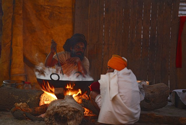 This picture taken on December 31, 2017 shows an Indian sadhu preparing food at a camp at Sangam, ahead of the Magh Mela festival, in Allahabad. The Magh Mela, which is known as a mini-Kumbh Mela, is scheduled to start January 2 and continue until February 13 with auspicious bathing dates throughout the 45 day period. (Photo by Sanjay Kanojia/AFP Photo)