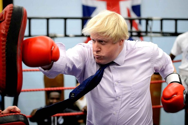 Mayor of London Boris Johnson boxes with a trainer during his visit to Fight for Peace Academy in North Woolwich, London, on October 28, 2014. Fight for Peace uses boxing and martial arts combined with education and personal development to realise the potential of young people in the borough at risk of crime and violence. (Photo by Leon Neal/AFP Photo)