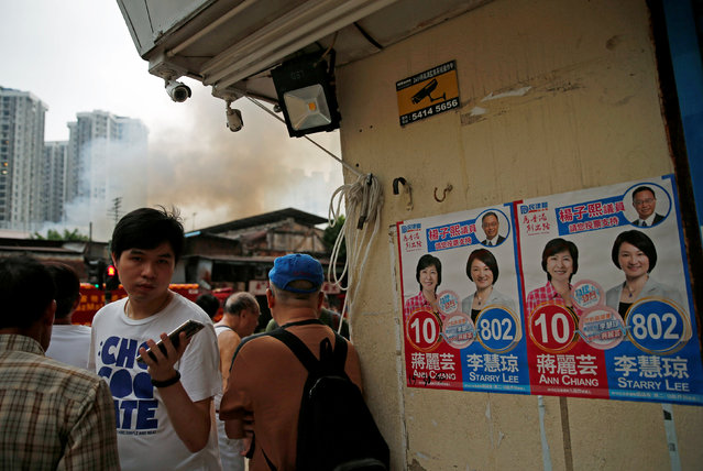 Posters of Ann Chiang (L) and Starry Lee, candidates from Democratic Alliance for the Betterment and Progress of Hong Kong are seen next to Yau Ma Tei Wholesale Fruit Market while smoke billows from the fire, on election day for the Legislative Council in Hong Kong, China September 4, 2016. (Photo by Tyrone Siu/Reuters)