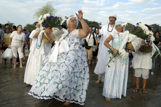 Faithful prepare to wade into the ocean to deliver their offerings to Yemanja, the African sea goddess, during a ceremony honoring the deity in Montevideo, Uruguay, Saturday, February 2, 2013. Thousands of worshippers come to the beach in Montevideo on her feast day, February 2, bearing candles, flowers, perfumes and fruit to show their gratitude for her blessings bestowed upon them. The belief in the goddess sprouts from Umbanda, a blend of religions that include African, Catholicism and Spiritism. (AP Photo/Matilde Campodonico)