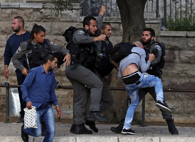 "Israeli border policemen scuffle with a Palestinian protester as they detain him before a protest near Damascus Gate outside Jerusalem's Old City October 8, 2015. A spate of ""lone-wolf"" stabbing attacks has alarmed authorities and unsettled Israelis, with Jerusalem's mayor urging people with gun licenses to carry their weapons and Israeli leaders vowing to quash the violence though apparently stumped over how to do so. (Photo by Ammar Awad/Reuters)"
