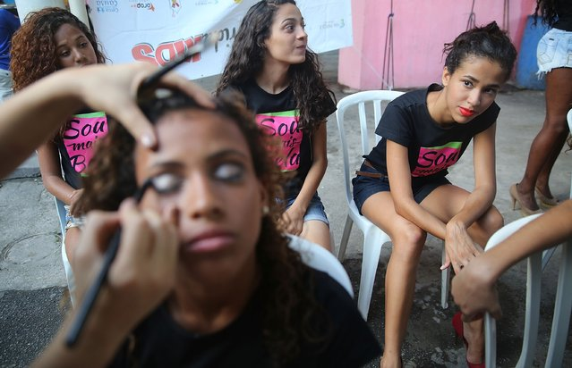 "A model is prepared with makeup at a fashion show thrown by ""Jacare e Moda"" in the Jacarezinho community, or ""favela"", on November 1, 2014 in Rio de Janeiro, Brazil. Models aged between 14-22, all residing in the North Zone of Rio, participated in the show. Around 1.6 million reside in the favelas of Rio. (Photo by Mario Tama/Getty Images)"