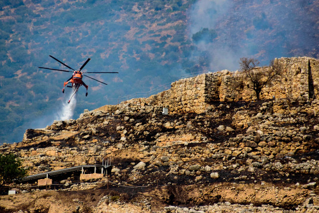 A firefighting helicopter drops water to extinguish flames during a wildfire near the archaeological site of Mycenae in the northeastern Peloponnese, on August 30, 2020. A wildfire broke out near the ruins of the Bronze Age stronghold of Mycenae in Greece on August 30, prompting the evacuation of visitors to the archeological site. (Photo by Eurokinissi/AFP Photo)