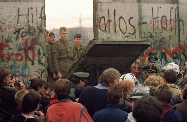 West Berliners crowd in front of the Berlin Wall as they watch East German border guards demolish a section of the wall on November 11, 1989. (Photo by Gerard Malie/AFP Photo)