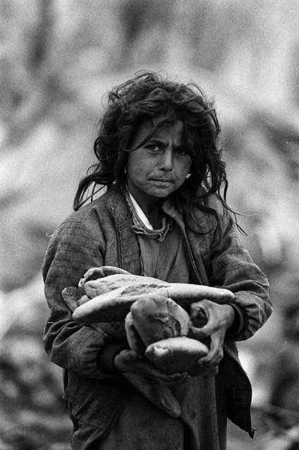 A young Iraqi Kurdish refugee holds loaves of bread in Cukurca refugee camp in Turkey April 8, 1991. (Photo by Srdjan Zivulovic/Reuters)