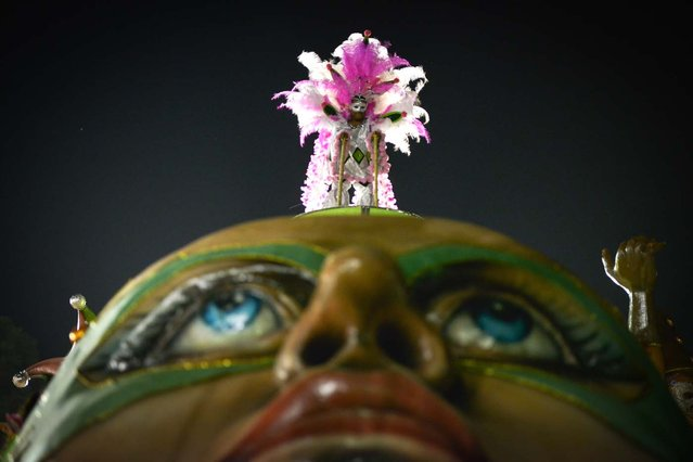 A reveller of Barroca Zona Sul samba school stands atop a float during the last day of the carnival parades at the Sambadrome in Sao Paulo, Brazil, on February 12, 2013. Barroca this year is focusing its carnival theme on the history of Jabaquara, an ethnically diverse district that includes Jardim Oriental, a community that is home to many Japanese. (Photo by Yasuyoshi Chiba/AFP Photo)