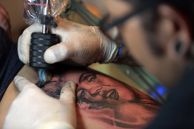 A woman has her leg tattooed during the VIII International Convention of Tattoo artists in Bogota, Colombia, Saturday, November 15, 2014. (Photo by Fernando Vergara/AP Photo)