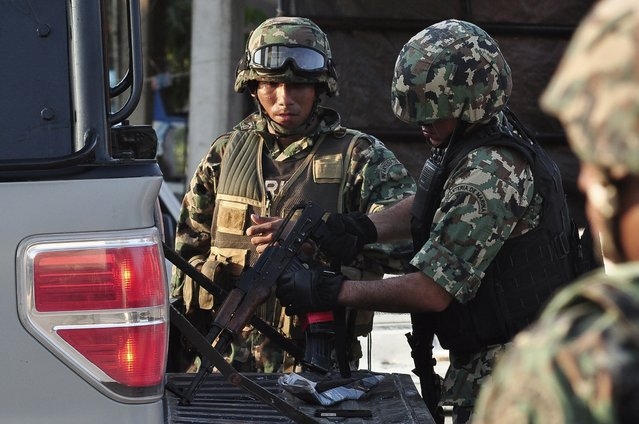 Marine soldiers inspect a weapon after a gunfight in the town of La Concepcion, on the outskirts of Acapulco November 15, 2014. A gunbattle between members of the community police and hitmen left at least four people, three attackers and one member of the police, dead, local media reported. The incident occured on Saturday afternoon when opposing protesters clashed over the planned construction of a dam. (Photo by Claudio Vargas/Reuters)