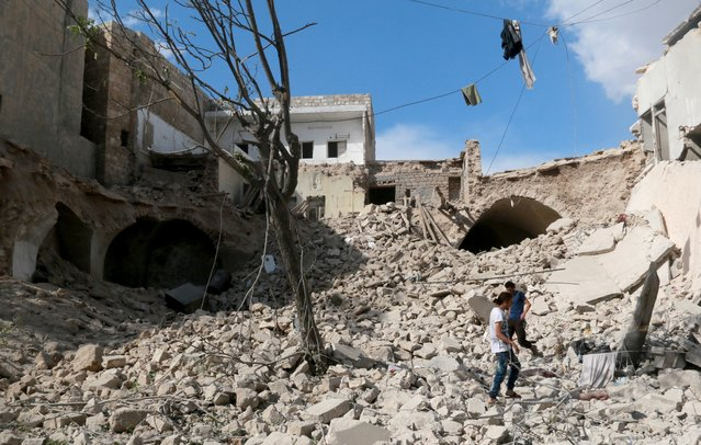 Syrians walk over the debris of a collapsed building after Syrian and Russian army carried out an airstrike on opposition controlled residential area at Maadi town of Aleppo, Syria on September 23, 2016. (Photo by Jawad al Rifai/Anadolu Agency/Getty Images)