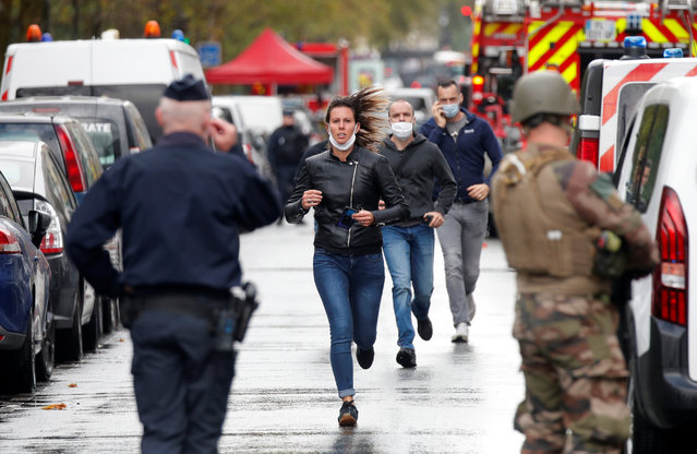People walk towards security forces at the scene of an incident near the former offices of French magazine Charlie Hebdo, in Paris, France September 25, 2020. (Photo by Charles Platiau/Reuters)