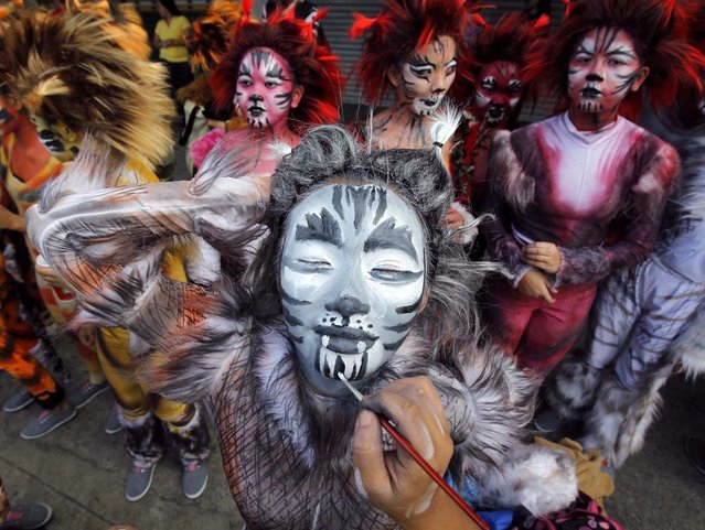 """A student has her face painted as part of her nature-inspired costume before participating in a parade for the Caracol festival in Makati city, metro Manila February 24, 2013. The annual Caracol festival, the """"Mardi Gras of Makati"""", is held as a tribute to mother nature. (Photo by Romeo Ranoco/Reuters)"""
