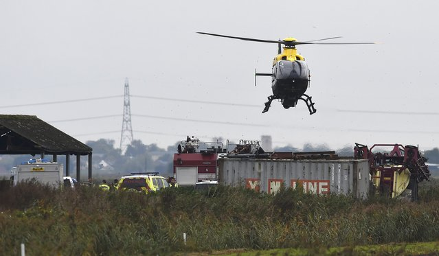A police helicopter hovers over the site of a plane crash Cambridgeshire, eastern England, Britain, October 21, 2015. One person was killed on Wednesday when a military aircraft, believed to be a fighter jet, crashed on farmland after taking off from a U.S. Air Force (USAF) base in eastern England. (Photo by Alan Walter/Reuters)