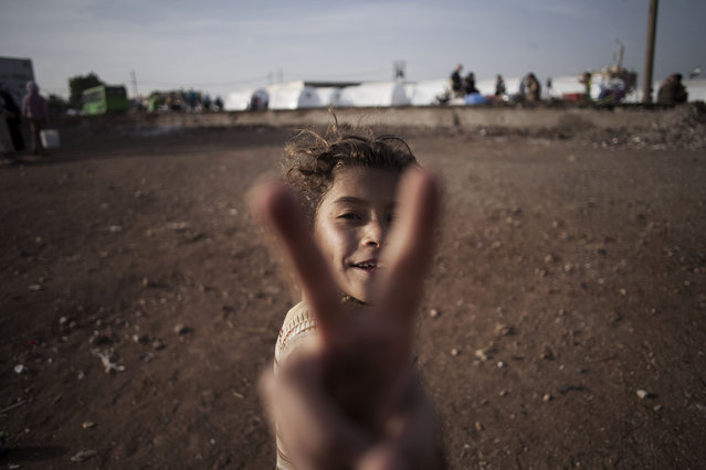 A Syrian girl, who fled her home with her family due to fighting between government forces and rebels, flashes the victory sign at a refugee camp near the Turkish border, Azaz, Syria, Sunday, October 7, 2012. (Photo by Manu Brabo/AP Photo)