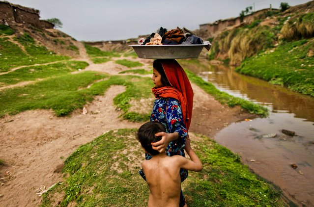 A refugee girl carries her laundry on her head after washing it in a polluted stream on World Water Day in a poor neighborhood on the outskirts of Islamabad, Pakistan, on March 22, 2013. The U.N. estimates that more than one in six people worldwide do not have access to 5 to13 gallons of safe fresh ater a day to ensure their basic needs for drinking, cooking and cleaning. (Photo by Muhammed Muheisen/Associated Press)